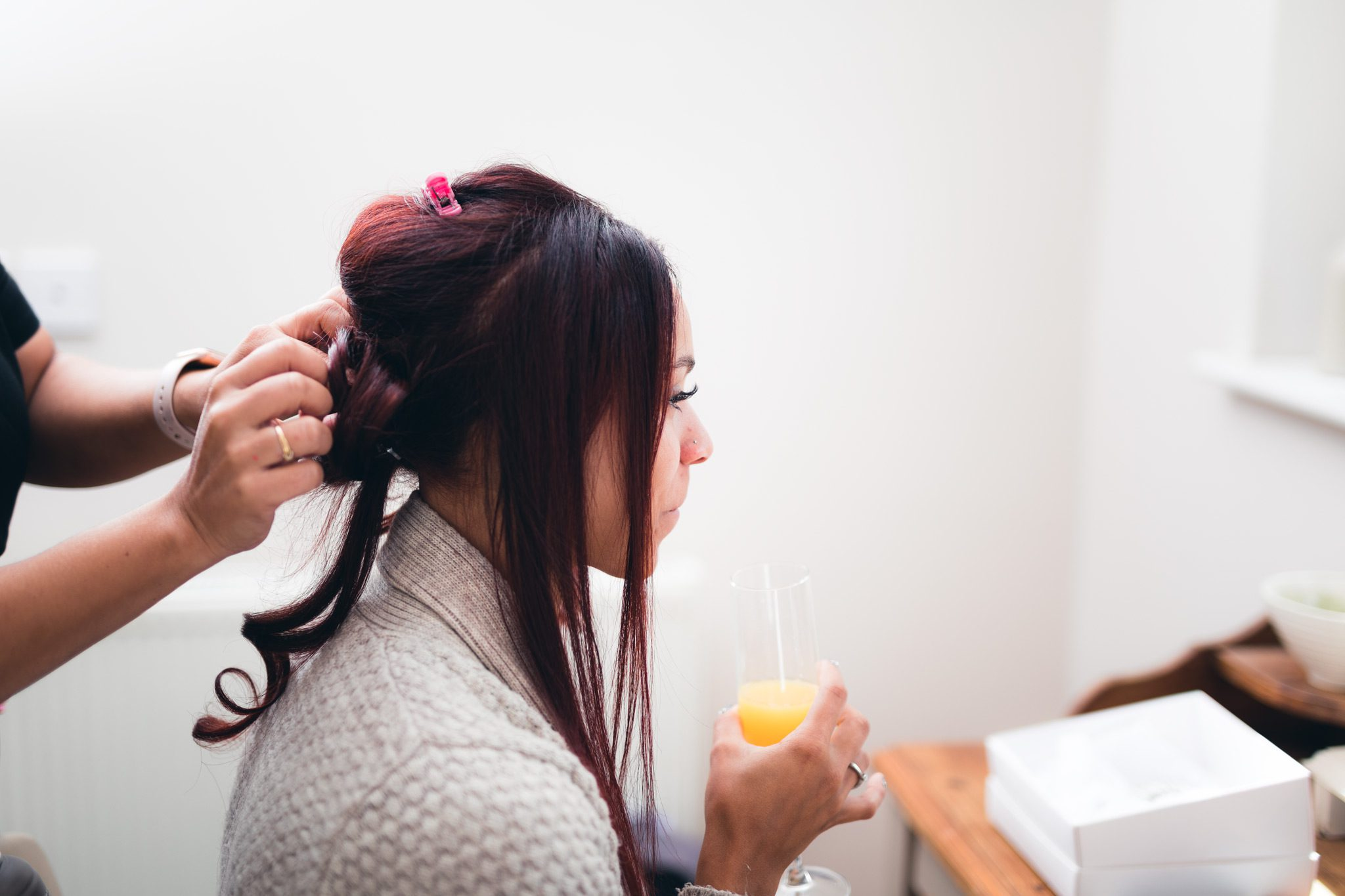 the bride enjoying a drink whilst having her hair done
