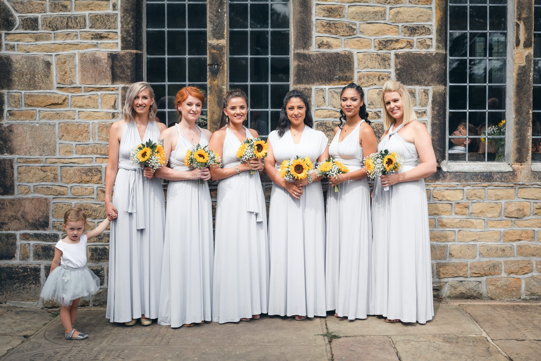Seven bridesmaids waiting outside of a church in the Peak District