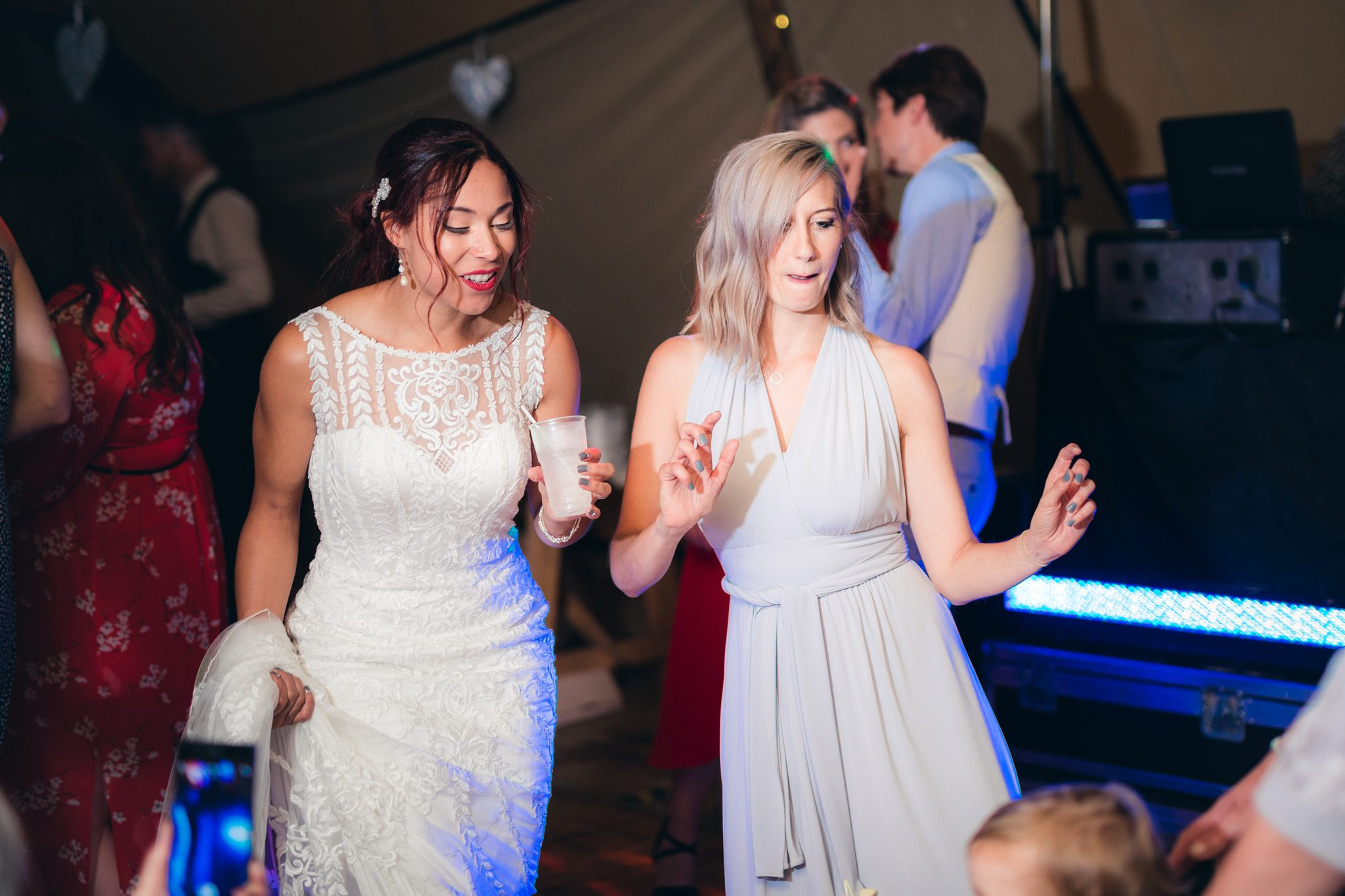 The bride and her bridesmaid dancing on the dance floor at a tipi wedding