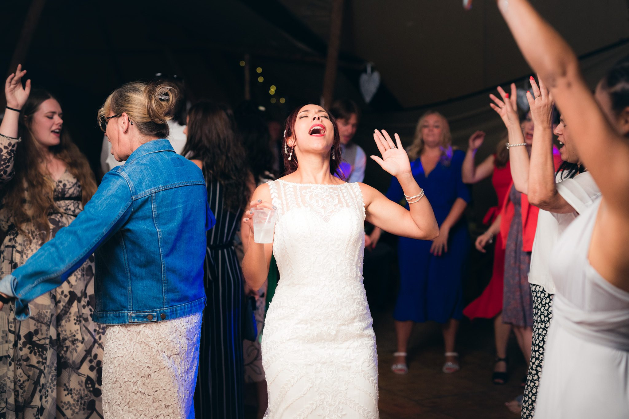 bride having a great time on the dance floor at a tipi weding in the Peak District