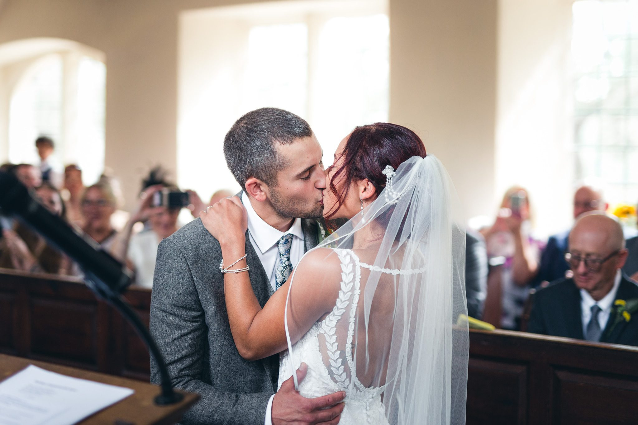 bride and grooms first kiss at a church in the peak district