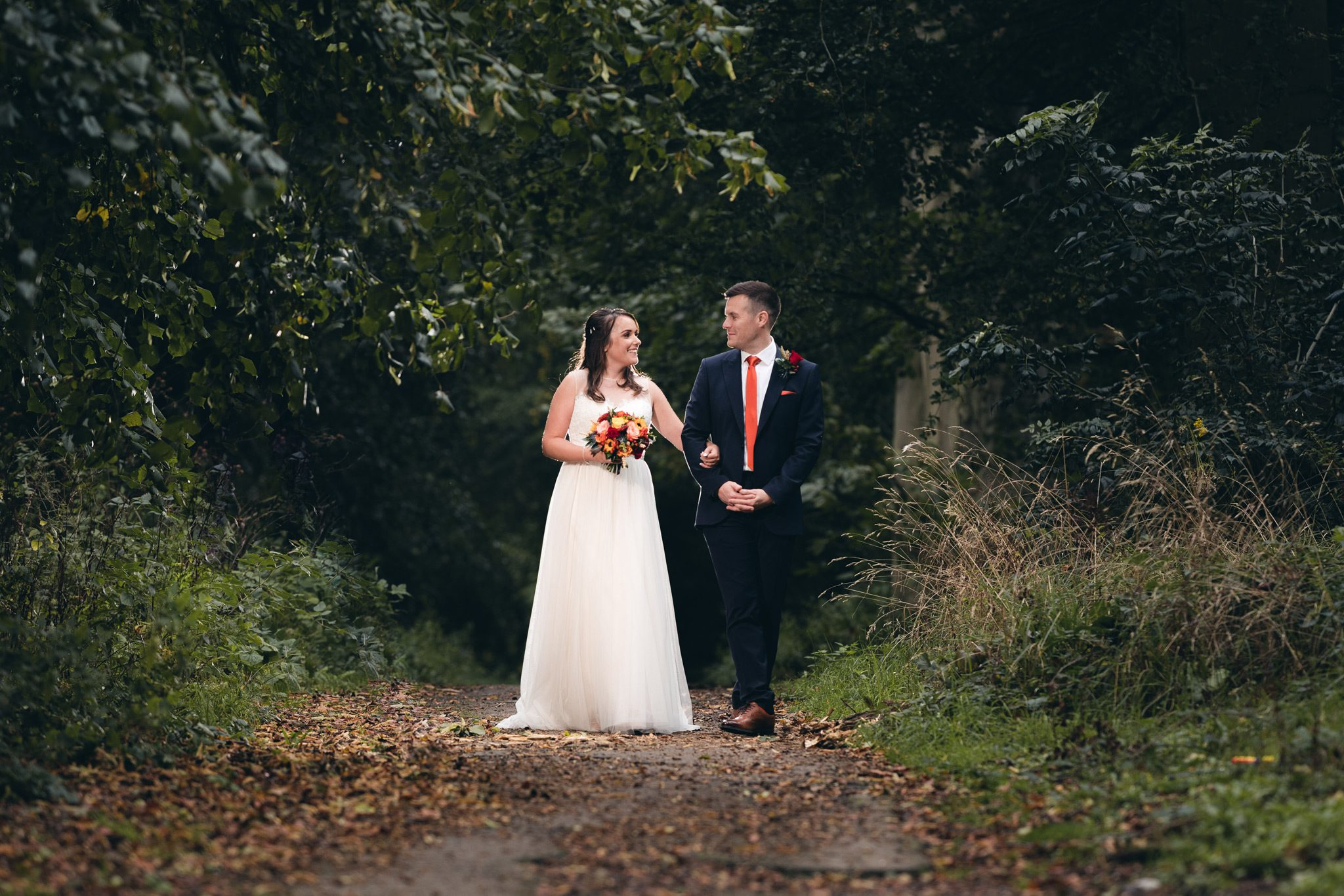 Bride and Groom walking through the woods